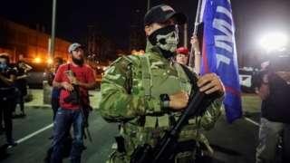 Em foto noturna, homem porta fuzil; atrás, outro homem armado e bandeiras com nome de Trump