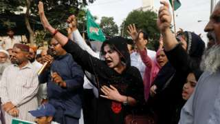 PML-N supporters raise their hands in protest in Karachi on 13 July