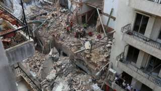Rescue workers clear through rubble in Beirut