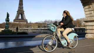 A cyclist wearing a protective mask rides a bike near the Eiffel Tower in Paris, France, 15 March 2021