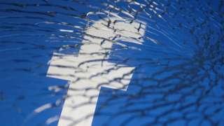 Facebook logo behind shattered glass
