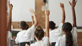 children in classroom raising their hands