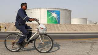 A worker rides a bicycle by oil tanks at an oil processing facility of Saudi Aramco.
