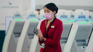 A Cathay Pacific staff member wearing a facemask next to a row of self-check in terminals in Hong Kong.