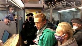 Alexei Navalny (hagati) n'umugore wiwe Yulia (i buryo) avugana n'umuporisi