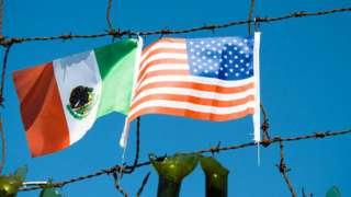 Arame farpado com bandeiras do México e dos Estados Unidos ao fundo