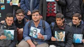 University of Tehran students hold pictures of victims during a memorial after the plane crash