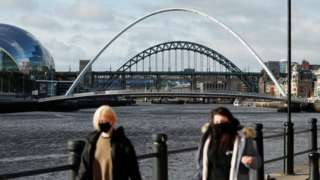 View of two women wearing masks with River Tyne bridges and the Sage Gateshead in the background
