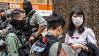 A woman is questioned by Kong Kong riot police