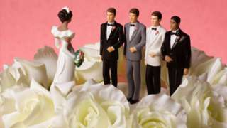 A wedding cake with figures of a bride and three grooms