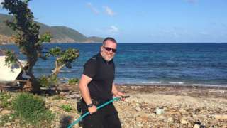 PC Gareth McSherry carrying a hose on a beach