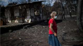 A woman wearing a mask walks in front of her burnt house following a wildfire at the village of Neos Voutzas, near Athens (26 July)