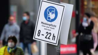 "People walk past a sign reading ""Mask is mandatory"" on a shopping street as the spread of coronavirus disease continues in Frankfurt, Germany, October 19, 2020"