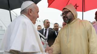 Pope Francis is greeted by Morocco's King Mohammed VI upon disembarking from his plane at Rabat-Sale International Airport