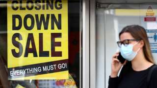 A woman wearing a protective mask speaks on the phone in front of a closed down store