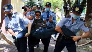 Протестующего уносят полицейские во время акции 6 июня в Алматы