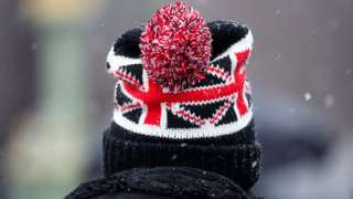 A person wears a Union Flag bobble hat during wintery weather in London
