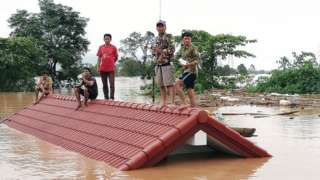 Lao villagers are stranded on a roof of a house after they evacuated floodwaters after the Xe Pian Xe Nam Noy dam collapsed in a village near Attapeu province