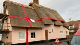 Thatched cottage tied with ribbon