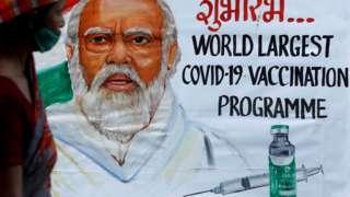 Man walking past a poster of PM Modi in Mumbai