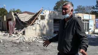 A man walks by a market in Tartar, Azerbaijan, damaged in a shelling attack