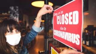 Woman hangs 'Closed for coronavirus' sign