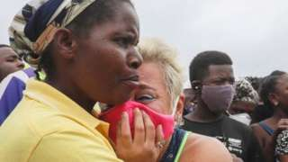 A woman cries as she waits for her son to arrive in Pemba on April 1, 2021, from the boat of evacuees from the coasts of Palma.