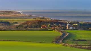 Windmill and North sea Weybourne and north Norfolk coast