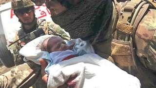 An Afghan security personnel carries a newborn baby from a hospital, at the site of an attack in Kabul on May 12, 2020.