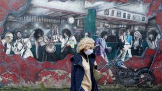 A woman walks past a wall mural during the resurging coronavirus outbreak in Galway, Ireland