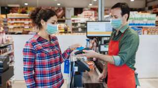 A customer pays at a supermarket till using her credit card