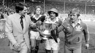 Ipswich Town manager Bobby Robson (left) and coach Cyril Lea escorted by players David Geddis and captain Mick Mills (hat) as they parade the FA Cup in triumph at Wembley Stadium.