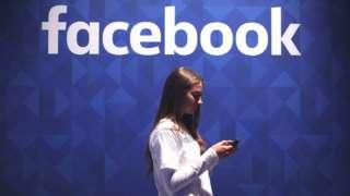 Youn woman checking phone under facebook logo