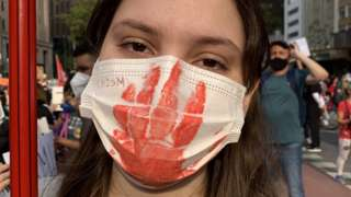 A woman wears a mask with a bloody hand print printed on it