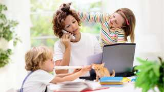 Woman working at home, with her children