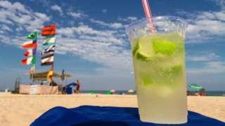 Um copo de caipirinha em area de praia, com pessoas e barracas ao fundo