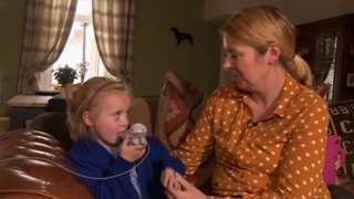 Harriet Corr uses her nebuliser while sitting next to her mum, Emma