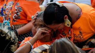 Indigenous women cry during a ceremony to mark the discovery of 750 unmarked graves at a Canadian residential school (1 July)
