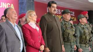 """Handout photo released by Miraflores presidential press office showing Venezuela""""s President Nicolas Maduro (C) flanked by his wife Cilia Flores (L) and Defense Minister Vladimir Padrino (R) during the 82nd anniversary ceremony of the Bolivarian National Guard at Military Academy, in Caracas on August 4, 2019"""