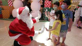 A man dressed as Santa Claus greets children at a shopping mall in Jakarta on December 25, 2020.