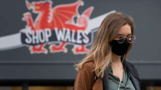 Woman in face mask with dragon on shop behind her in Cardiff