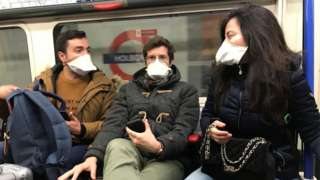 People on a tube wearing face masks