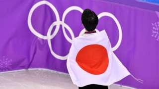 Un athlète japonais avec le drapeau japonais sur le dos se tient devant les anneaux olympiques.