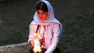 فتاة تشعل القنديل عند معبد لالش