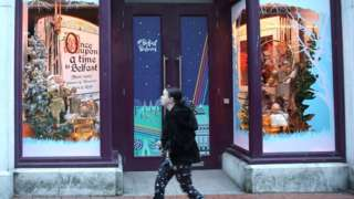 A woman walks past a closed shop in Belfast