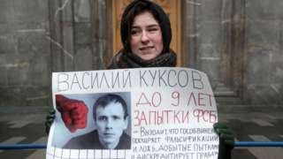 A protester stands outside an FSB office holding a photo of one of the convicted Set members