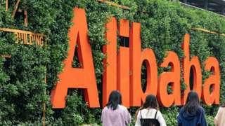 Four women walk past an Alibaba sign.
