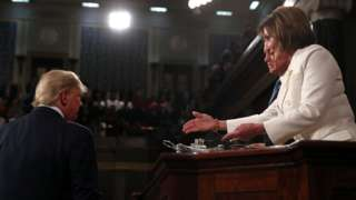 Speaker of the US House of Representatives Nancy Pelosi (R) extends her hand to US President Donald Trump