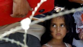 """A girl looks on from behind barbed wire while waiting with her family to enter into Macedonia from Greece, on the border line between the two countries, near southern Macedonia""""s town of Gevgelija, on Wednesday, Aug. 26, 2015."""