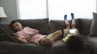 Two kids sitting on the sofa